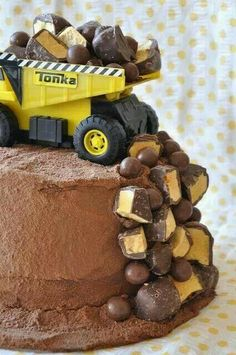 Make any flavor cake, frost with chocolate icing then dust with cocoa. Place a toy dump truck on top and place candies like rocks.