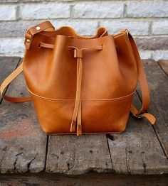 Adorable and versatile in smooth or oil-tanned leather, this bucket bag makes the task of carrying your daily goods a stylish occasion