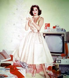 Elizabeth Taylor in a studio Christmas still in the late 1950s. The Monogram car model is a 1957 Cadillac, and the television is an RCA color set.