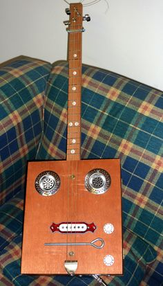 Cigar Box Guitar (Made from a jewellery box body, nails for frets, shirt button fret markers, picture hook tail piece, sink strainer sound holes, steel studding nut.)