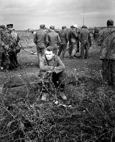 German POWs captured during the early fighting of the Battle of Anzio are photographed behind barbed wire in a temporary collection area. While the others mill about, one soldiers sits with a resolute glare. The Battle of Anzio began on 22 January 1944 with the Allied amphibious landings (Operation Shingle) in the areas of Anzio and Nettuno and would only end after a stalemate lasting five months. Near Anzio, Lazio, Italy. February 1944.