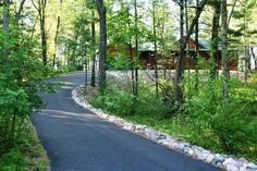 Asphalt driveway with rock edging and natural landscapeing - front yard landscaping ideas with rocks