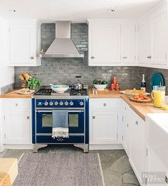Even the most classic, beautiful white kitchens can benefit from a jolt of color. Here, blue and gray accents, eye-catching appliances, and wood countertops keep the cook space looking smart.