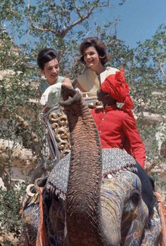 "At Jaipur, sitting in an elaborately carved howdah, Jackie and her sister [Lee Radziwill] ride on a trumpeting female elephant, newly painted and spangled for the show."" Published in the March 30, 1962 article of LIFE titled, ""Jackie Leaves Her Mark on India and Vice Versa."""
