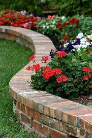 Brick flower bed border doubling as a casual bench. Small retaining wall with brick on edge capping. Better straight, not curved, for our space. Front yard by the porch and sidewalk. - Flower Beds and Gardens Flower Bed Borders, Raised Flower Beds, Garden Borders, Raised Beds, Front Flower Beds, Garden Border Edging, Lawn Edging, Small Retaining Wall, Retaining Walls