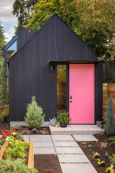 The garage door was replaced with a new entry to the building, featuring a custom steel canopy over the front door. The door is painted Benjamin Moore Flamingo's Dream to better contrast with the black-stained, tight-knot vertical cedar siding. Architecture Durable, Architecture Photo, Seattle Architecture, Black House Exterior, Garage Exterior, Backyard Cottage, Cedar Siding, Wood Siding, Front Door Colors