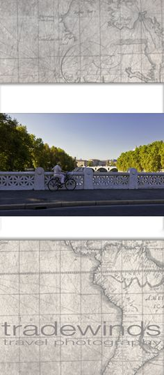 A bicyclist enjoys  the view from a bridge in rome