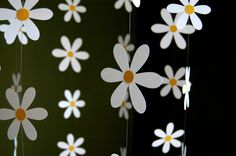 This darling, daisy mobile is strung with 56 white, card-stock daisy with yellow-gold centers. Flowers hang delicately and move beautifully in a light breeze. Total length from ring is approx. 30 and total width is about 16. Mobile hangs easily from the ceiling from a small adhesive