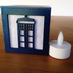 This laser-cut box is painted a nice metallic T.A.R.D.I.S. blue! The same design is on all four sides of the box so it can be placed anywhere in a room. During the day the box is metallic blue with a white background, but when the lights are out and you place a flameless tea light candle (included) underneath, the white areas will light up a bright blue. The box is made of laser-cut MDF, which is then painted to the color you see here. Size: 3 inch cube Color: Metallic Blue My light boxes…