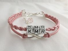 This infinity bracelet with a custom name or message is made of hand braided leather cord and features FOUR silver-toned acrylic letter beads of your choice gathered with a second band with an infinity charm.    Infinity charms are the universal symbol of forever and are frequently used to demons...