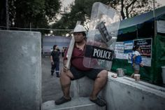 WAITING IT OUT: An antigovernment protester held a police shield and stick near the Government House in Bangkok, Thailand, Tuesday. Prime Mi...