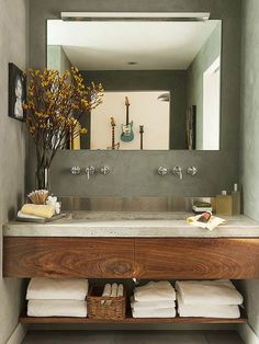 Create a just-right bathroom vanity by utilizing an entire sink alcove. This modern vanity with two partial drawers fits snugly into a small space; a lower shelf leaves plenty of room for towels. A concrete countertop and stainless-steel backsplash provide contemporary contrast to the rustic wood drawer fronts.