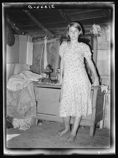 Girl standing in front of bureau in shack home. Tin Town, Caruthersville, Missouri. 1938 Aug. Library of Congress.