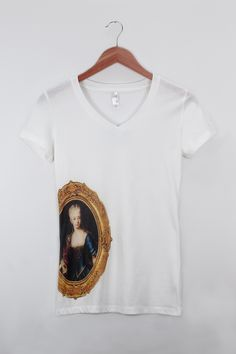 Maria Theresa Painting of Maria Theresa framed with Baroque motif on the front , and her name and reign on the back. Direct full color print on light weight and super soft white Sporty-V by Next Level Apparel. $34.95