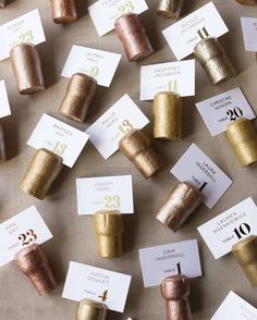 To hold the escort cards in New Year's Eve style, Champagne corks (ordered online in bulk) were hand-painted and scored by Carrie, McCormick, and other friends and family members—one of several projects that occupied the weeks leading up to the wedding. New Years Wedding, New Years Eve Weddings, New Years Eve Party, Deco Nouvel An, Inexpensive Wedding Centerpieces, Champagne Corks, Gold Champagne, Wedding Champagne, Wedding Sparklers