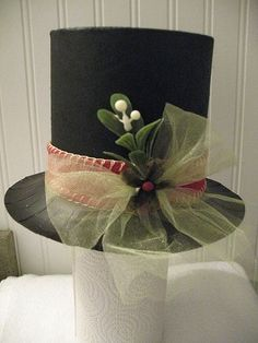 Frosty hat made from 1/2 oatmeal box and paper plate, sprayed black; then embellished. Unseen on other side is a melting snow drip coming from top of hat made with glue and glitter. by carlene