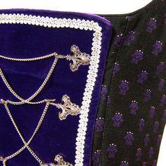 Sehr schönes Vintage Dirndl aus Brokat in den Farben lila und schwarz, mit einem Latz aus lila Samt, hübsch verziert mit silberner Posamentenborte und einer Kettenschnürung vorne.  Es ist hinten...