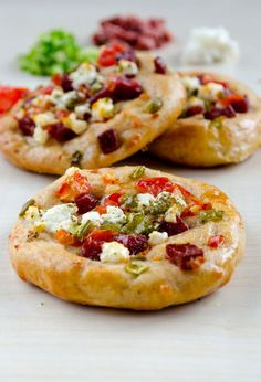 Mini pizzas topped with cheese, tomatoes, peppers and sujuk | giverecipe.com | #pizza #baking