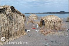 Straw huts in the El Molo fishing village with Lake Turkana in background, Northern Kenya