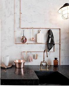 hoe cool is dit! Koperen buizen, in een paar bochten gebogen (met een buigijzer). Je bevestigt de buizen met koperen zadels aan de muur. Zo vormen ze handige rails om keukengoed aan op te hangen.