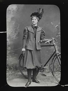 Lantern Slide Showing Woman Wearing Rational Dress -- essentially baggy plus fours and a nicely fitting jacket.  I dunno about that hat on a bike, though.  ; )