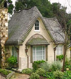 """This English-inspired design fea-  tures a stucco exterior and a shingled roof with rolled eaves to simulate thatch, as well as wavy or """"crooked"""" ridge lines to simulate age."""