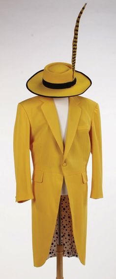 Yellow single-breasted wool coat with tails, lined in white satin with black polka dots. With a wide-brimmed yellow hat, with black trim and striped feather. Worn by Jim Carrey as Stanley Ipkiss (alias, the Mask) in The Mask Halloween Makeup, Halloween Ideas, Halloween Costumes, Jim Carrey The Mask, Jim Carey, The Mask Costume, Yellow Coat, Masquerade Party, Haunted Houses