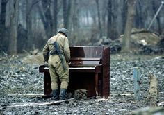 Soldado russo tocando um piano abandonado em uma floresta na Chechênia em 1994.