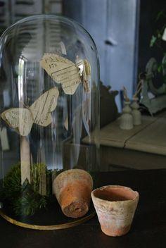 Des papillons en papier découpés dans du papier ancien sous une cloche de verre