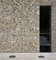 Slot window contrasting rough material with sharp smooth glass.