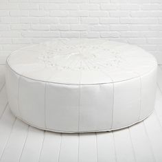 The Moroccan Leather Ottoman in white is decoratively stitched and makes the perfect coffee table or ottoman.