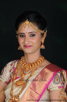 Traditional Southern Indian bride, Asha wears bridal silk saree and jewellery for her Muhuratam. Makeup and hairstyle by Swank Studio. Jhumkis. Maang tikka. Berry lips. Silk sari. Tamil bride. Telugu bride. Kannada bride. Hindu bride. Malayalee bride. Bridal Saree Blouse Design. Indian Bridal Makeup. Indian Bride. Gold Jewellery. Statement Blouse.  Find us at https://www.facebook.com/SwankStudioBangalore