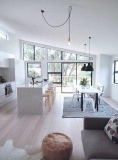 White kitchen, pale wooden floor, black feature window/door