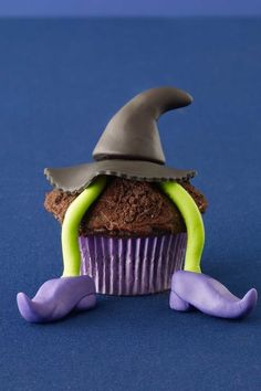 Wicked Witch Cupcake: A fondant Wicked Witch of the East-like figure dangles deliciously from her perch: a cupcake topped with chocolate frosting and a dusting of crushed chocolate wafer cookies. Find more cute and creepy Halloween cupcake recipes and ideas that are easy to make here.