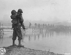 WWII 3rd Battalion troops in Burma cross a river using bamboo footbridge while mules are led through the water alongside the bridge. Photographer unknown.