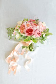 Yummy coral and blush Garden Rose bouquet with streaming ribbons. | by Gavita Flora.
