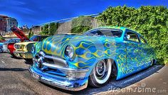 Custom painted 1950 American blue Ford Customline with yellow flames on display at car show in Melbourne, Australia.