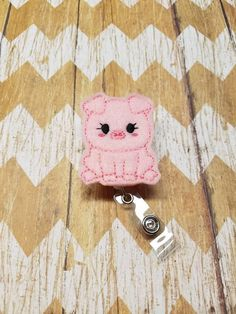 A pink pig feltie attached to a retractable badge reel. Badge reel extends to approx. 24 inches Please choose the style clip you prefer when ordering...