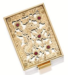 GOLD AND RUBY VANITY CASE, BOUCHERON, CIRCA 1950.  The rectangular vanity case, set with a concealed mirror exterior overlaid with carved openwork plaque of butterflies, flowers and leaves studded with cabochon rubies, opening to reveal a hinged compartment for powder and a mirror, mounted in 18 karat pink gold and silver, signed and numbered BT No 875012