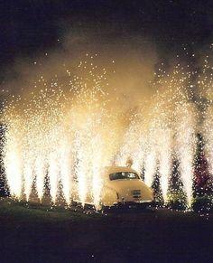 Entrada espectacular en la celebración de la boda con un coche clásico y un montaje de cohetes y fuegos artificiales