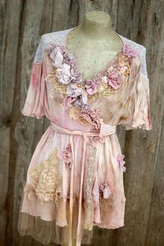 Whimsy vintage crinkled viscose tunic/wrap jacket or blouse.. altered couture; reworked with intricate details to discover. Hand dyed in uneven shades of dusty beige, cream, blush, pale pink; the tunic is adorned withtorn silk embroidered florals and petals at hems, old lace pieces,