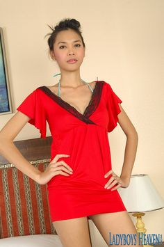 """Asian TS """"Bang"""" in a tight red dress posing on the bed. #ladyboy #shemale #tranny #tgirls"""