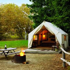 Luxury Camping, Canvas tents with adjacent bathhouses take the edge off camping with warm comforters, willow beds, and firepits perfect for barbecuing dinner (with burgers and s'mores delivered to your front flap for an extra charge).