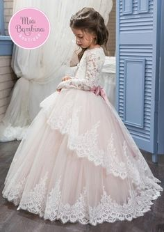 The Arlington ball gown style flower girl dress has a princess appearance. The lace bodice features long floral lace sleeves, atie-back waist and a lace corset