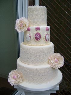 Four tier wedding cake with edible lace, cameos with bride and groom initials and sugar flowers