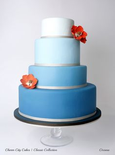 Classic Oceana by Charm City Cakes - A name so fitting for it reminds you of the beautiful ocean and its waves with it's blue ombre color. This four-layered cake is beautifully accented with silver ribbons and orange sugar flowers.