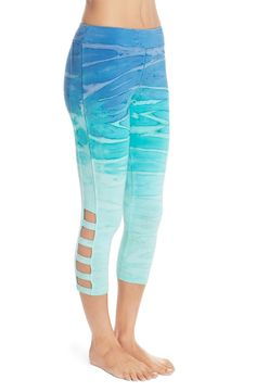 Soft, stretchy performance leggings feature a flatting ultra-wide waistband and stylish caged cutouts at the cropped hems.
