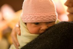 """I made two variations of the hat pattern. The first (the cuffed hat) has a delicate braid and keeps the """"rough"""" back of the cable away from baby's face. It does require more yarn & more knitting time, as you are essentially knitting an extra 1 ½ inches or more of stockinette stitch for the cuff."""