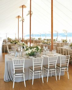 neutral linens, white chivari chairs and pretty centerpieces make this waterfront reception perfection. Design by @Lisa Phillips-Barton Vorce and Mindy Rice. Photography by: Aaron Delesie #wedding #summerwedding