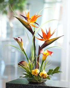 """An intricate design of birds of paradise and calla lilies interwoven into the fingers of a large philodendron leaf. A centerpiece with amazing realism in color and texture. Tall grass and cymbidium orchid blooms add the finishing touches. It's designed in a shallow 9"""" diameter glass bowl with our clear acrylic water and natural pebbles. It's a wonderful permanent floral design for your home or office."""